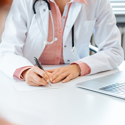 Doctor writing an online doctor's note for a patient.