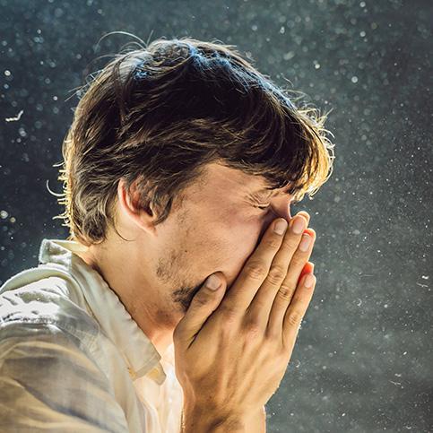 man sneezing because of allergies